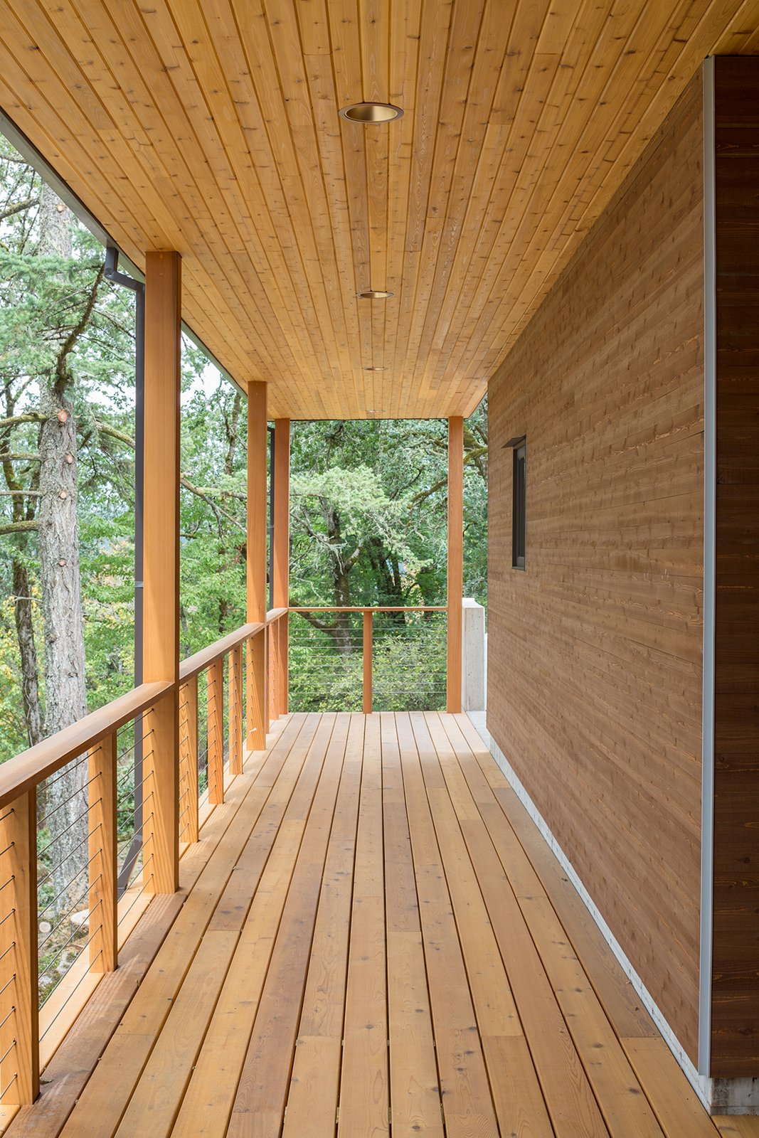 The covered walkway is enveloped by cedar planks and lush oak canopies.  Sunset Knoll House by Richard Brown Architect from Boards, Battens, and Bevels: Wood Board Siding Types and Their Uses