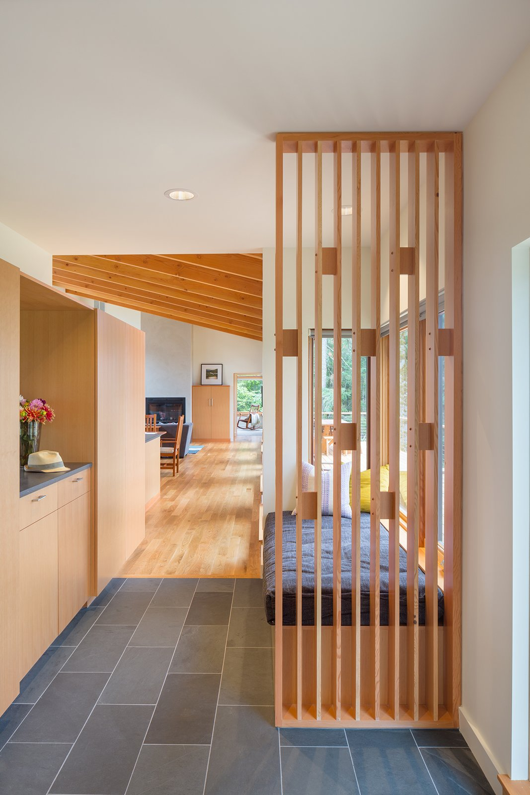 A playful wood screen greets visitors at the front entry, as well as providing support for a cushioned bench seat. Durable materials such as the Doug Fir cabinetry, White Oak flooring and a slate tile floor provide warmth and longevity.  Sunset Knoll House by Richard Brown Architect