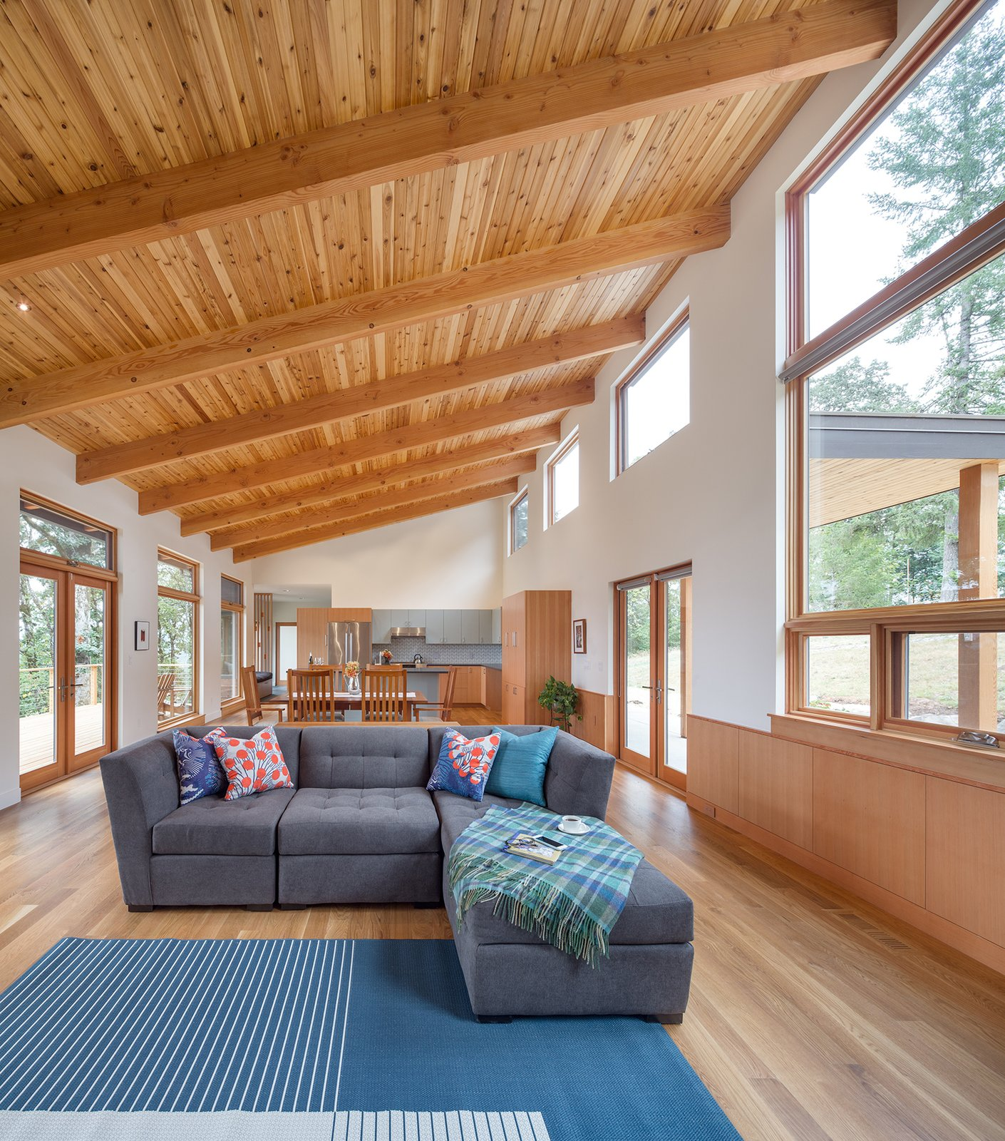 The great room, housed under a dramatic tongue and groove Cedar soffit, is flanked by views towards the East and West.  Sunset Knoll House by Richard Brown Architect