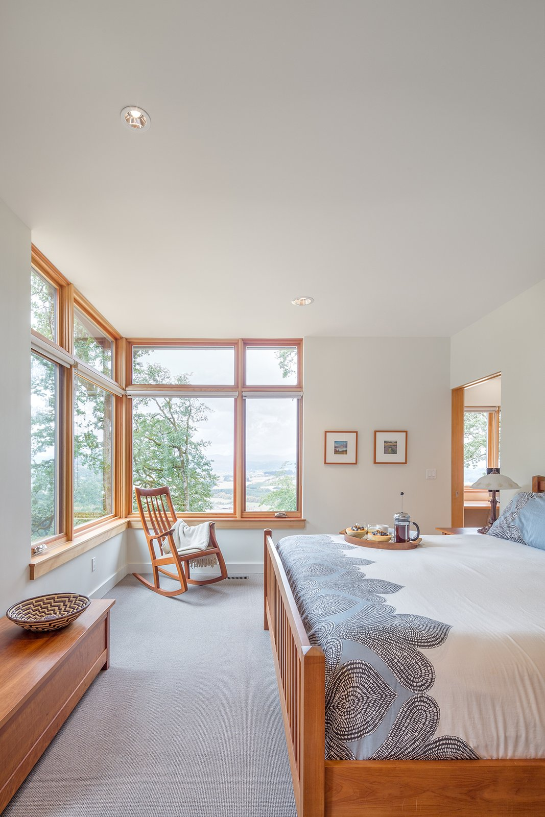 Full height corner windows in the master bedroom frame views towards the Yamhill Valley beyond.  Sunset Knoll House by Richard Brown Architect