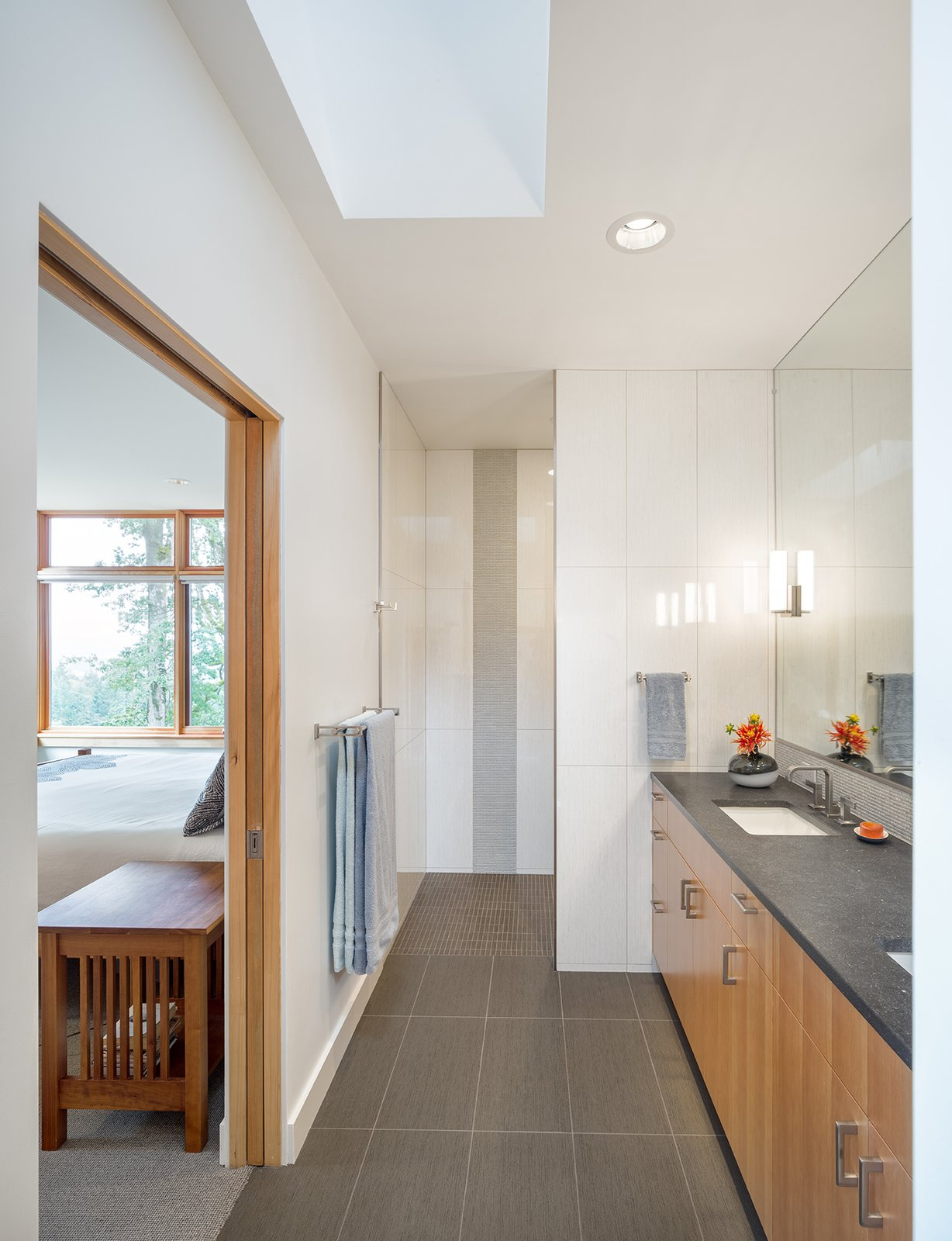 A sculptural skylight bathes the master bathroom in natural light.  A single level of tile floor allows easy access to the full height glass shower at the room's end.  Sunset Knoll House by Richard Brown Architect