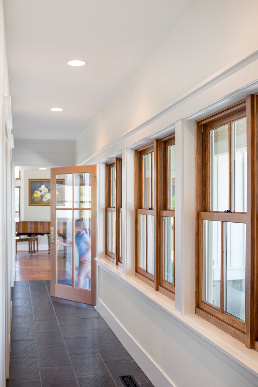 A row of single hung wood windows defines the entry hallway with views towards the front porch.  Shadowood House by Telford+Brown Studio Architecture