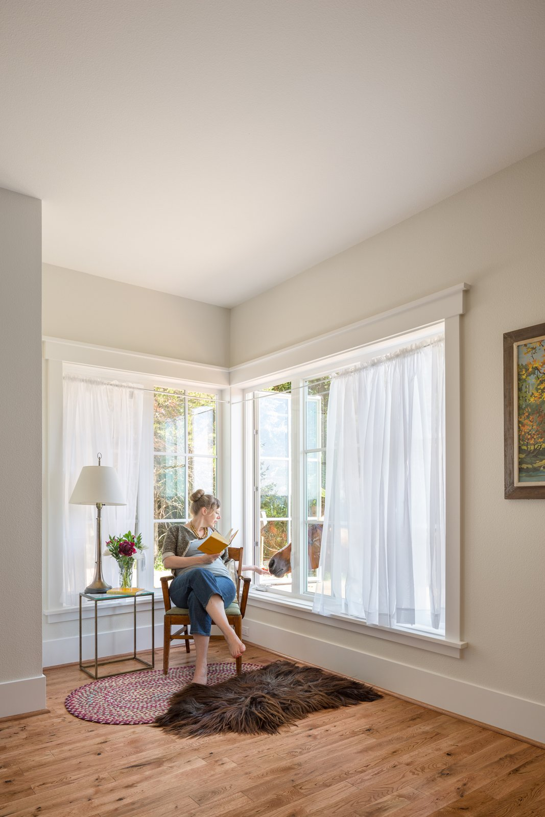 A reading nook, furnished with corner casement windows, welcomes an unexpected guest.  Shadowood House by Telford+Brown Studio Architecture