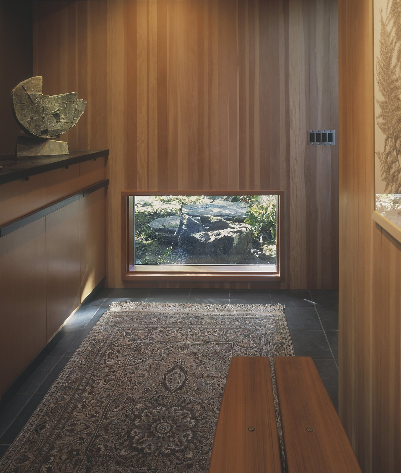 A low window frames the view of the garden's quiet fountain, set within a series of basalt boulders.  Wood paneled walls and slate floors are in keeping with the home's original 1949 materials.  Belluschi Addition by Richard Brown Architect