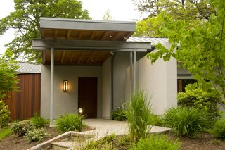 A Mahogany wood soffit cantilevers over the home's entry.