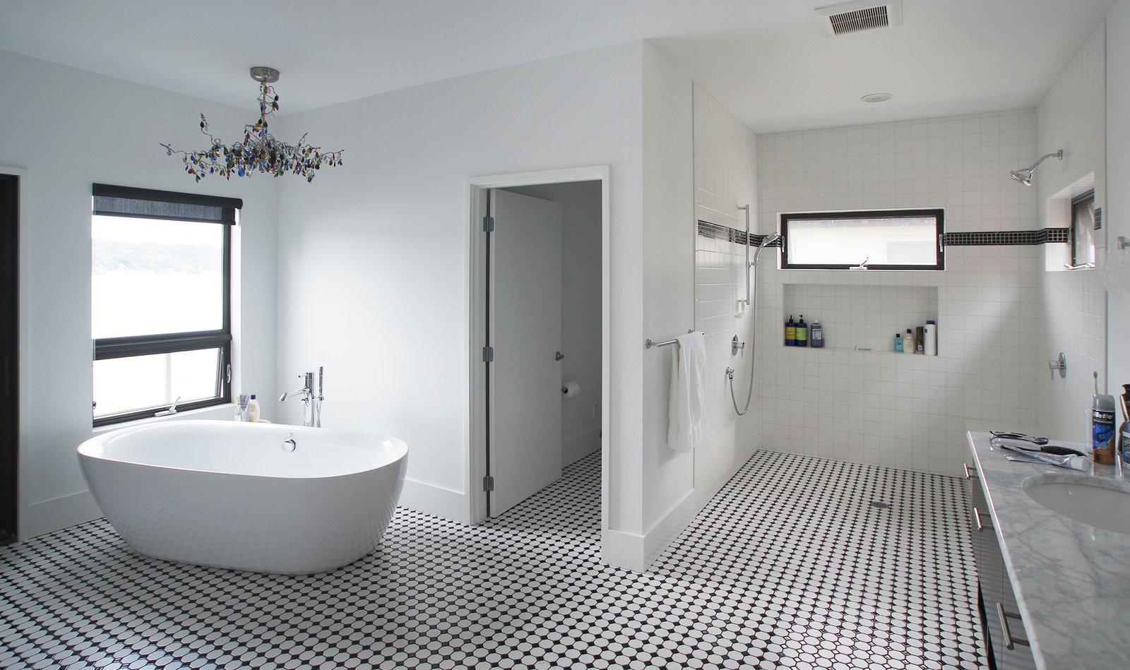 This black and white bathroom is open to the master suite as well as the deck and view beyond.  Lake Washington Home by Atelier Drome