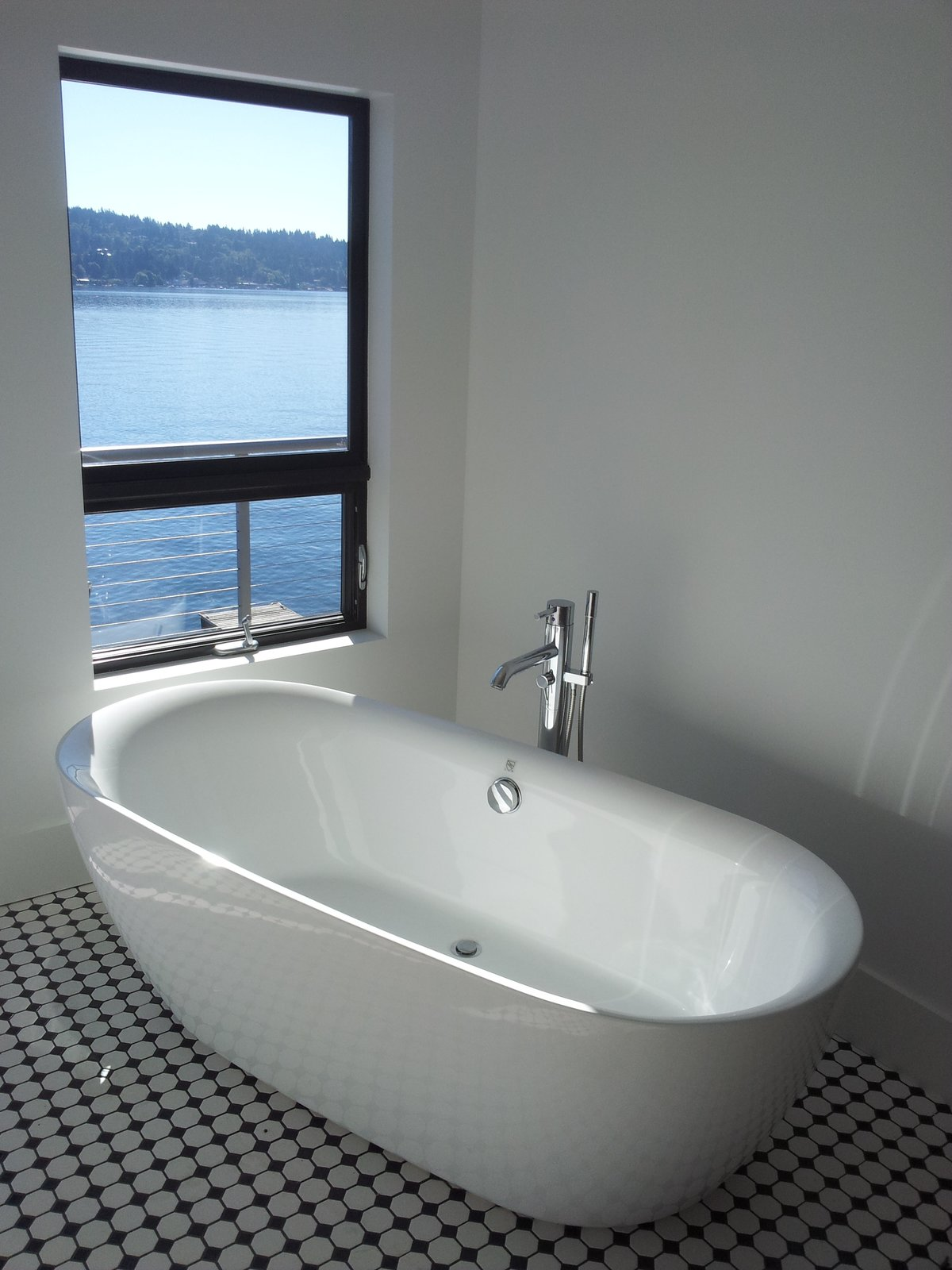 This freestanding tub allows the homeowners to site and enjoy the view during a soak.  Lake Washington Home by Atelier Drome