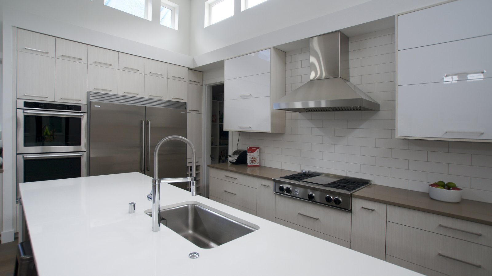 A neutral color palette is modernized with glossy finishes, a subway tile backsplash, and stainless appliance accents. This is a kitchen that will highlight and draw attention to the food, becoming a blank canvas for the owners to personalize.  Modern Courtyard Home by Atelier Drome