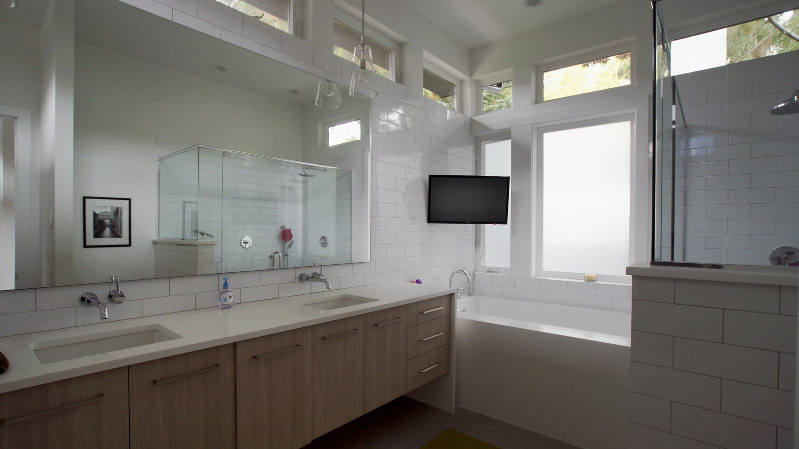 The master bathroom is a light-filled space of relaxation with a large bathtub as well a spacious shower. The tile backsplash provides a modern finish and every convenience was added to truly make this a room of leisure.  Modern Courtyard Home by Atelier Drome