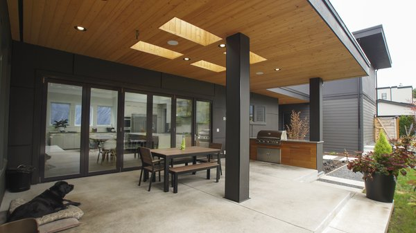 The covered patio and built-in barbecue make the backyard perfect for outdoor living.  Modern Courtyard Home by Atelier Drome
