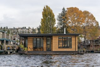 This floating home by Atelier Drome features a wraparound Ipe deck that is accessible from every room. The building is clad in horizontal cedar siding that adds style and warmth to the structure sitting on Lake Union. A cedar slat screen provides privacy from the dock.