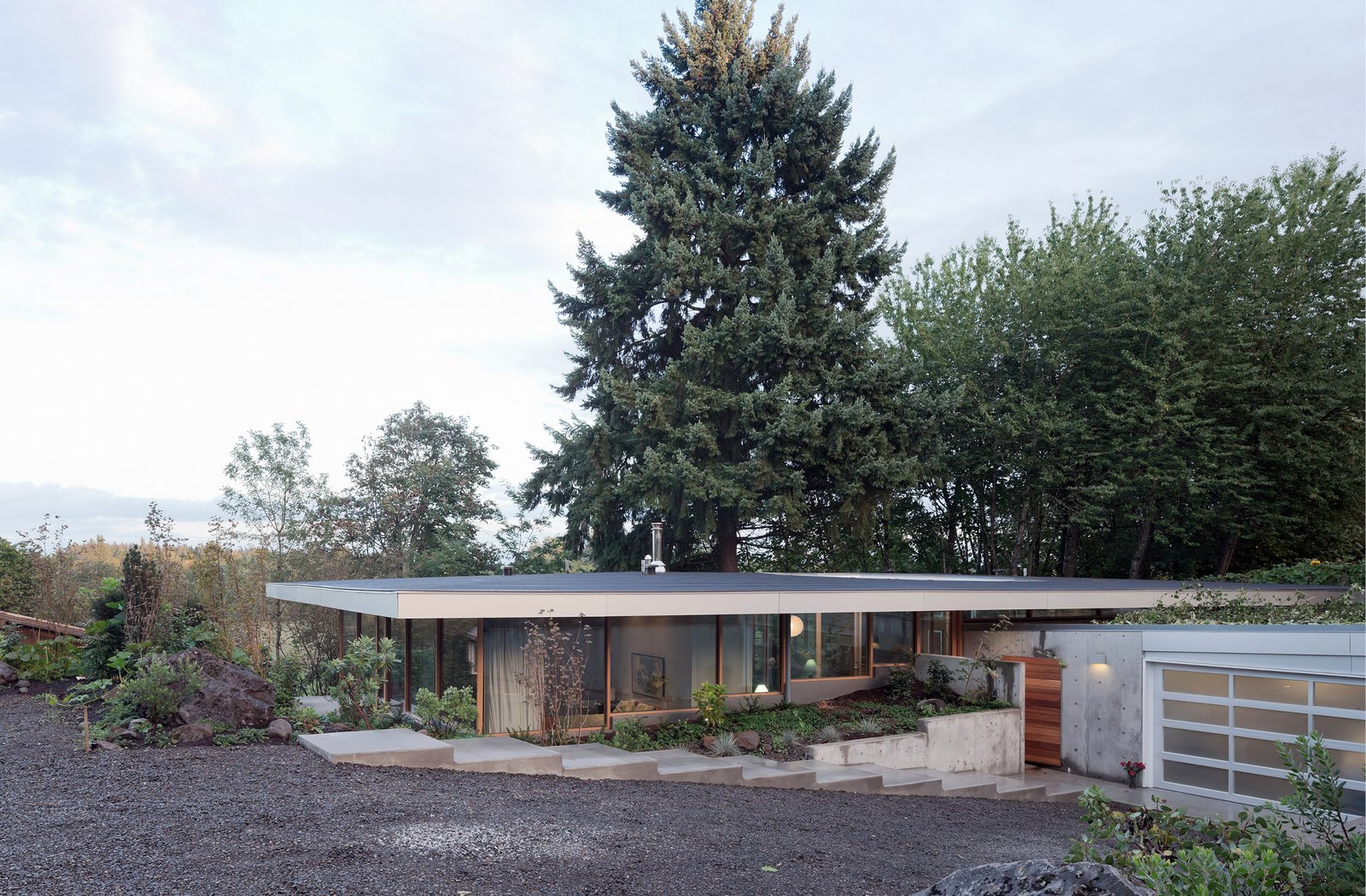 """In response to the demand to live harmoniously with nature and community, the Courtyard House is conceived as a canopy structure: a single volume framed between a cantilevered concrete slab below and a roof """"umbrella"""" above.  The Courtyard House"""