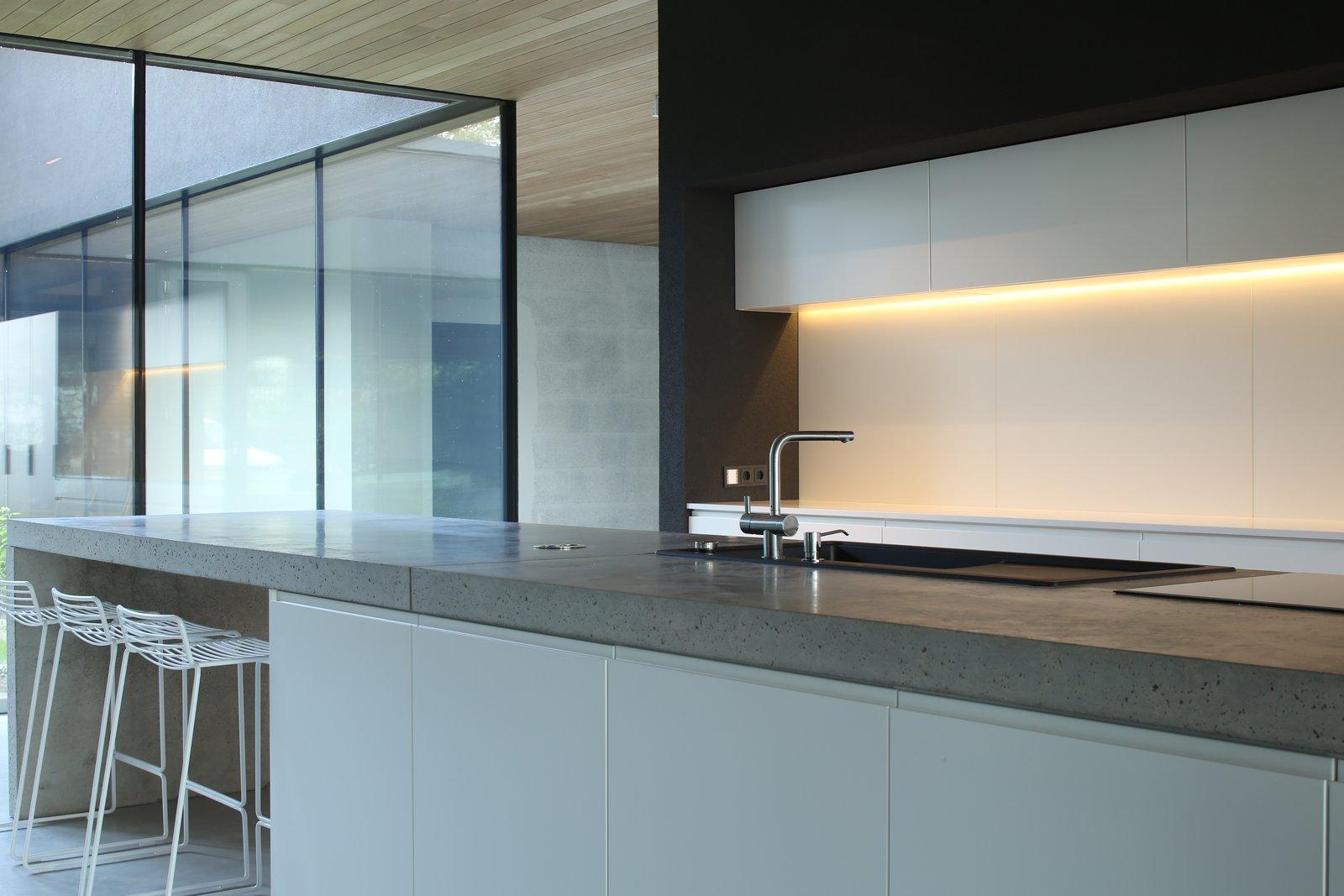 Open kitchen with view to the atrium and cherry trees   Karhusaari by Alvardag