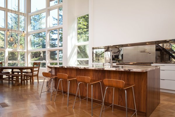 Island countertop and mirrored backsplash are the decorative elements in the minimally ornamented space.