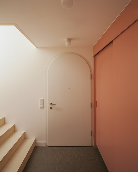 Upon entering into this 1950s home in Germany, visitors are greeted by a wall of storage in a dusty pink hue, giving the space warmth and efficient closet space in one fell swoop.