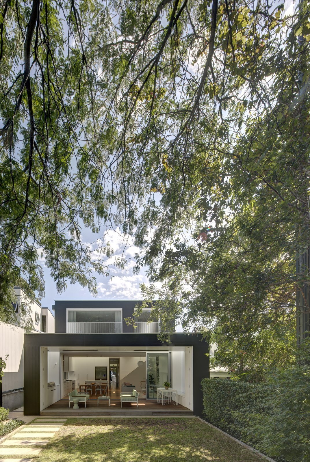 Outdoor, Back Yard, Trees, Shrubs, Walkways, and Grass The rear of the house opens to the garden, creating a layering of spaces from inside to out.  Inner West House by Andrew Burns