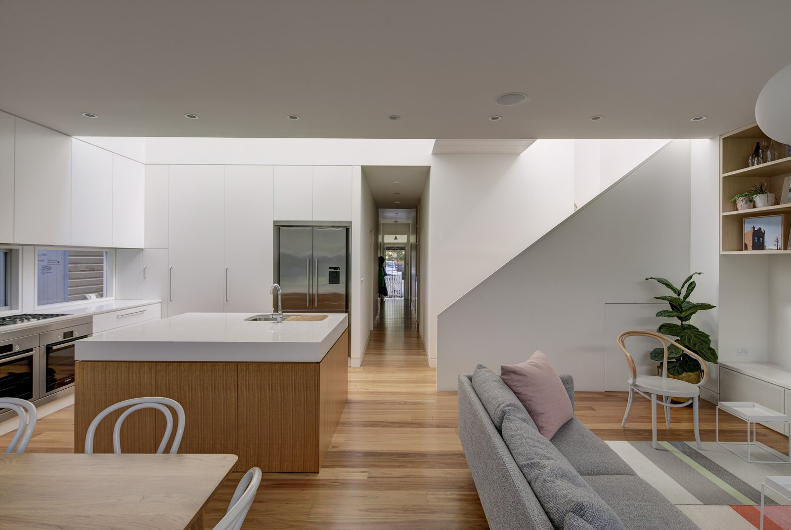 Kitchen, Engineered Quartz Counter, White Cabinet, Medium Hardwood Floor, and Ceiling Lighting Interior spaces are simple and understated. Natural timber in light tones contrasts with white walls, lit by washes of sunlight.  Inner West House by Andrew Burns