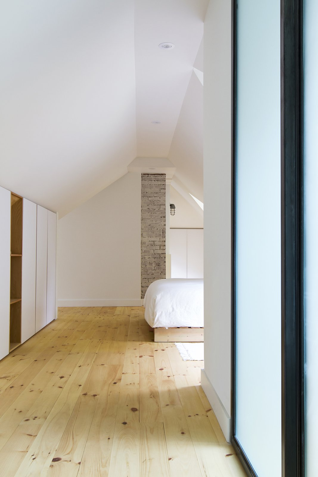 Bedroom, Wardrobe, Bed, Ceiling Lighting, Wall Lighting, and Light Hardwood Floor The master bedroom's simple design highlights the ancestral chimney.  L'Eau Vive by FÉLIX & Co.