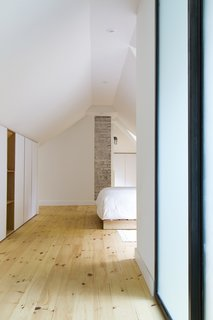 The master bedroom's simple design highlights the ancestral chimney.