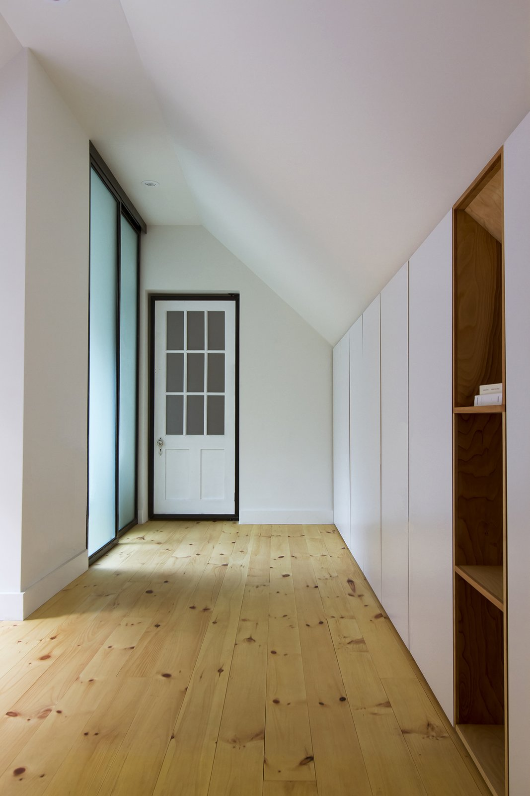 Bedroom, Wardrobe, Shelves, Ceiling Lighting, and Light Hardwood Floor The master bedroom is equipped with built-in furniture in the lower part of the roof and with a small private bathroom.  L'Eau Vive by FÉLIX & Co.