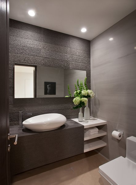 In Golden Beach, Florida, a new residence was designed with a minimalist, zen-inspired approach that carried through to even the small powder room, where the focal point is on a sculptural sink and a textured tile wall behind the sink.