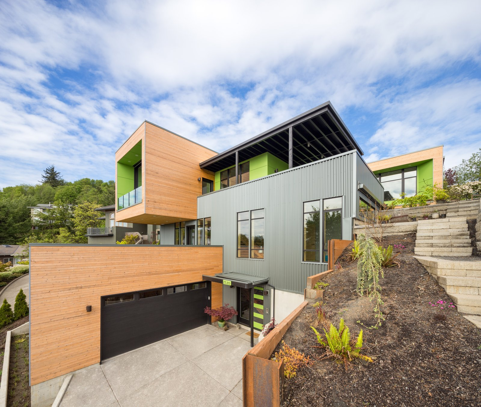 Exterior, House Building Type, Wood Siding Material, and Metal Siding Material Stacked volumes stepping up the slope  Panavista Hill House by Steelhead Architecture