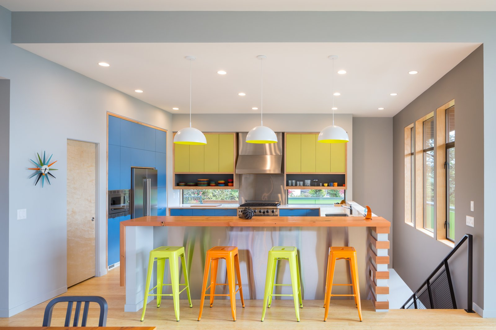 Kitchen, Quartzite Counter, Wood Counter, Colorful Cabinet, Laminate Cabinet, Medium Hardwood Floor, Pendant Lighting, Recessed Lighting, Refrigerator, Range, Range Hood, Microwave, and Undermount Sink Kitchen  Panavista Hill House by Steelhead Architecture