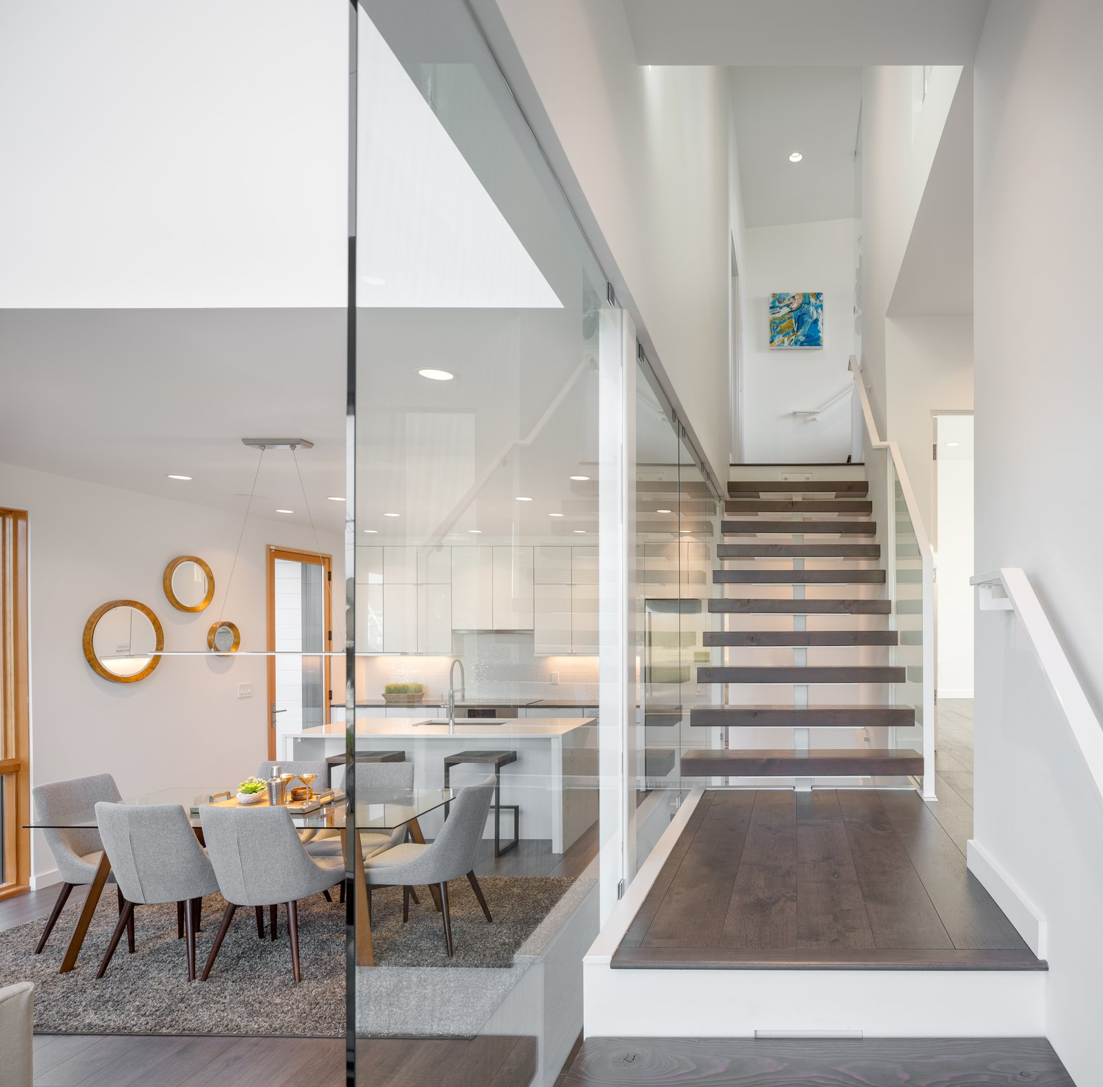 Staircase, Wood Tread, and Glass Railing The floating stairs opening to each split level  Lightbox 23 by Steelhead Architecture