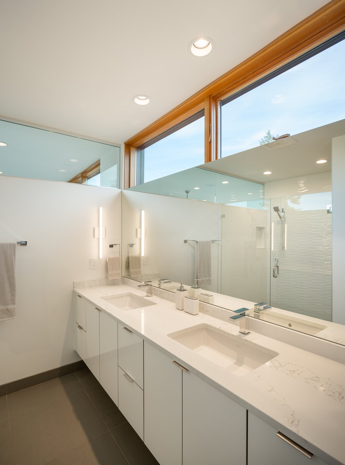 Bath Room, Porcelain Tile Floor, Porcelain Tile Wall, Wall Lighting, Undermount Sink, Recessed Lighting, Engineered Quartz Counter, and Open Shower Master bath with ribbon of windows and clerestory glass  Lightbox 23 by Steelhead Architecture