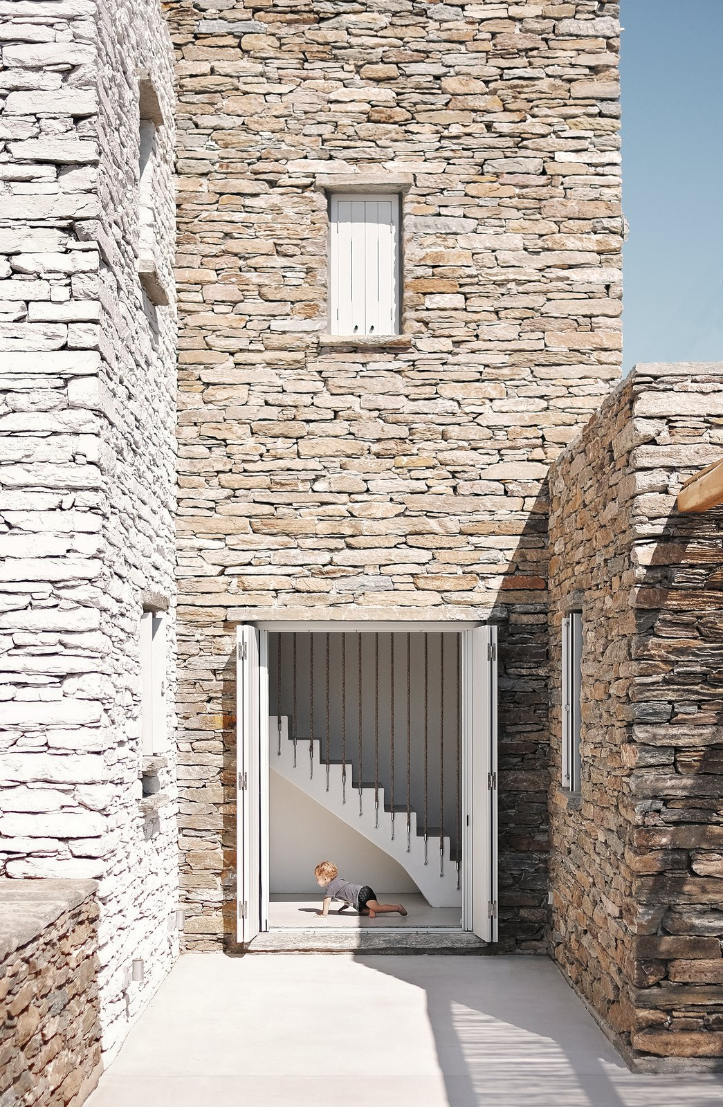 Exterior, Stone Siding Material, and House Building Type Ground floor patio  ROCKSPLIT house by COMETA ARCHITECTS