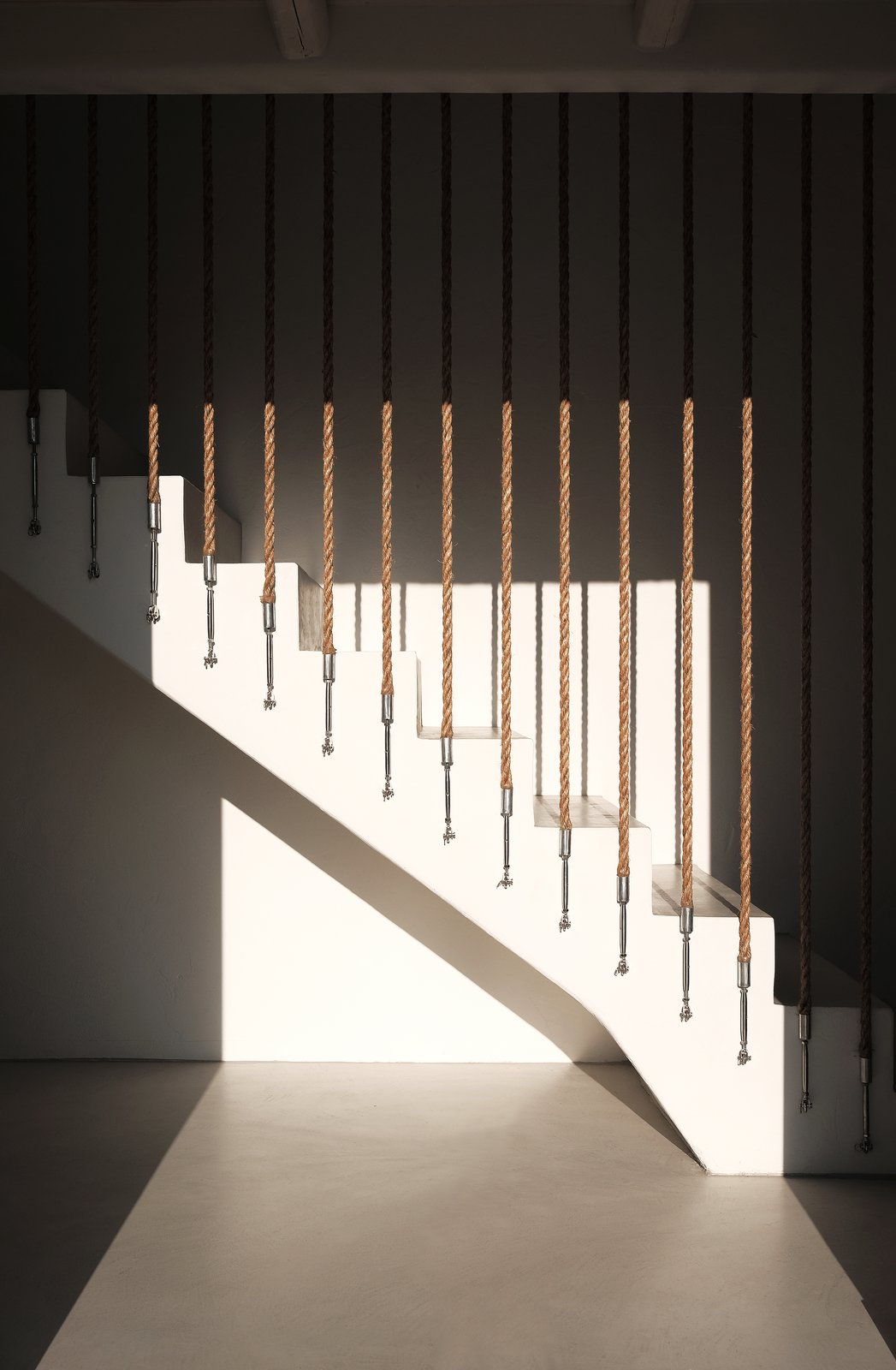 Interior stairs in the afternoon  ROCKSPLIT house by COMETA ARCHITECTS