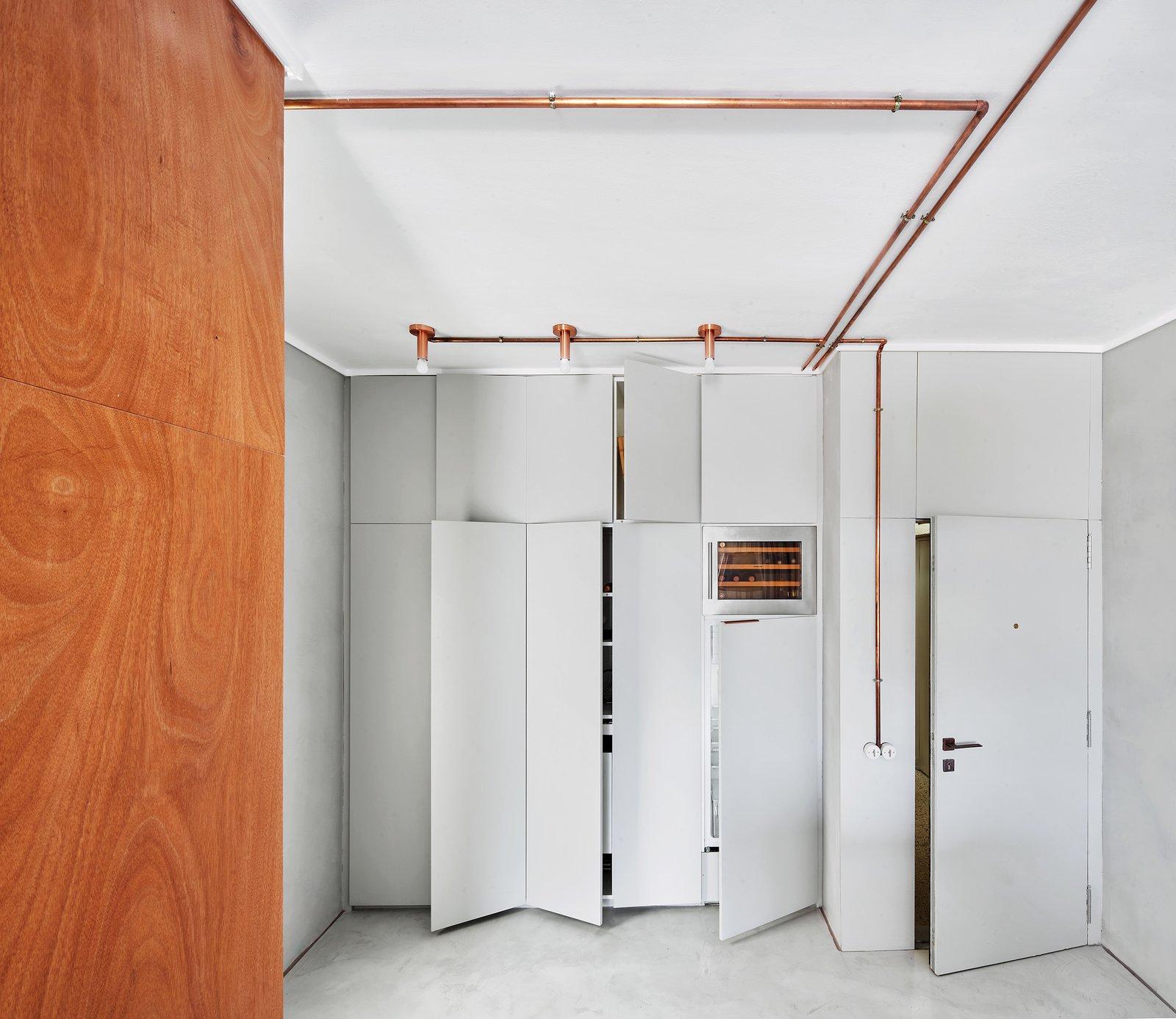 Kitchen, Wood, Refrigerator, Concrete, Concrete, Wood, Ceiling, and Wine Cooler Entrance along with built in closets, fridge & vinotecca  Best Kitchen Concrete Refrigerator Wood Photos from The Marina Apartment