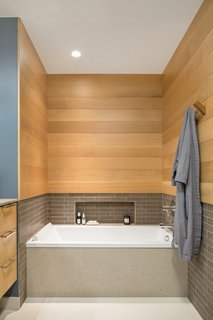 Mixed materials are presented in the tub alcove