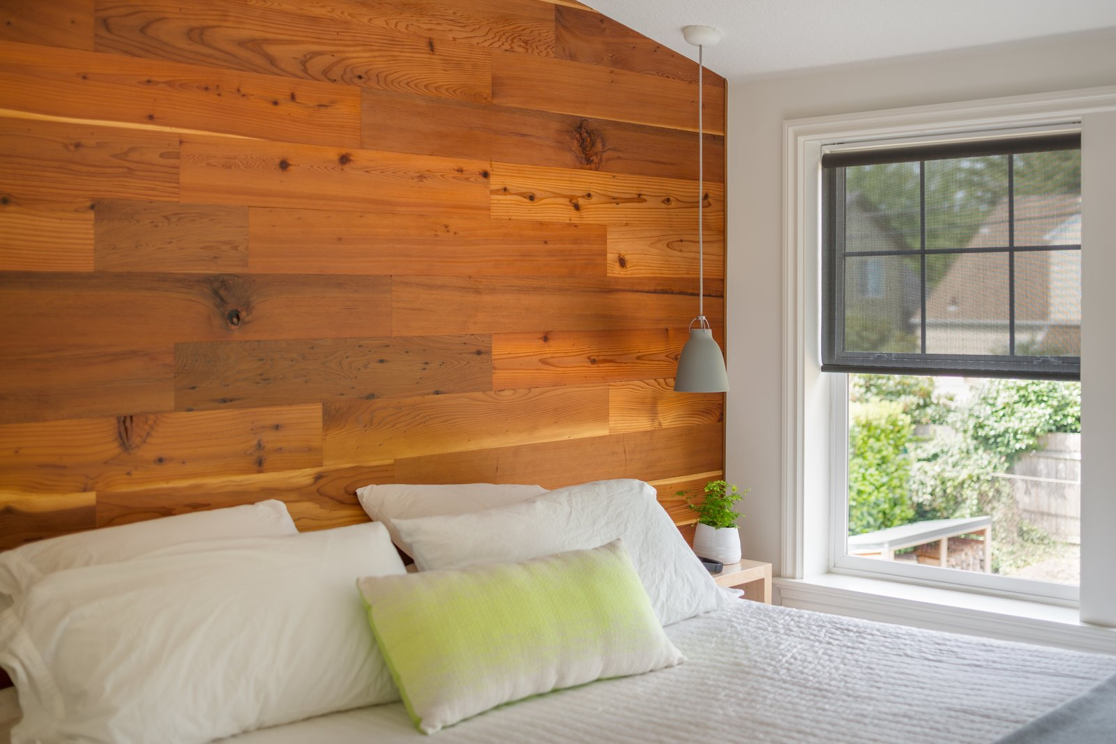 Cozy and minimalist, the wall becomes the headboard and focal point  Tagged: Carpet Floor, Bedroom, Pendant Lighting, and Bed.  Hurst Avenue by Guggenheim Architecture + Design Studio