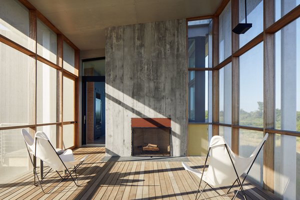 """The fireplace extends the season,"" says Ryall. ""The owners probably use that porch six months out of the year."" The design team formed the fireplace's concrete facade using rough wood boards to give it a rugged texture."