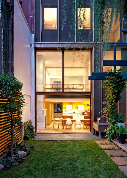 Viewed from the backyard, Greenwich Village Townhouse by Ryall Sheridan Architects gives off a warm, earthy glow.