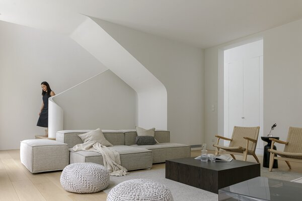 The gentle curves of the staircase soften the minimal, rigid lines in the open-plan living space, repeated in the linear sofa by Thai brand and the tactile CH25 amchair by Hans Wegner for Carl Hansen & Son