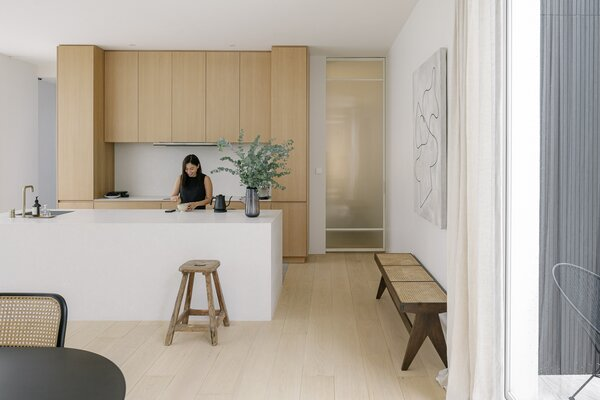 Full- height timber cabinetry and a white kitchen maintains the home's open, airy feel, while the loose furniture stays with the minimal approach