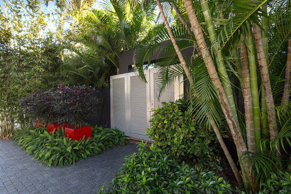 Outdoor, Front Yard, Garden, Hardscapes, Gardens, Trees, Walkways, Raised Planters, Shrubs, Pavers Patio, Porch, Deck, Landscape Lighting, and Metal Fences, Wall A dynamic entrance to the garden framed by mass plantings and bright sculptural containers sets the scene for the tropical garden behind the closed doors.  Von Phister by Craig Reynolds Landscape Architecture
