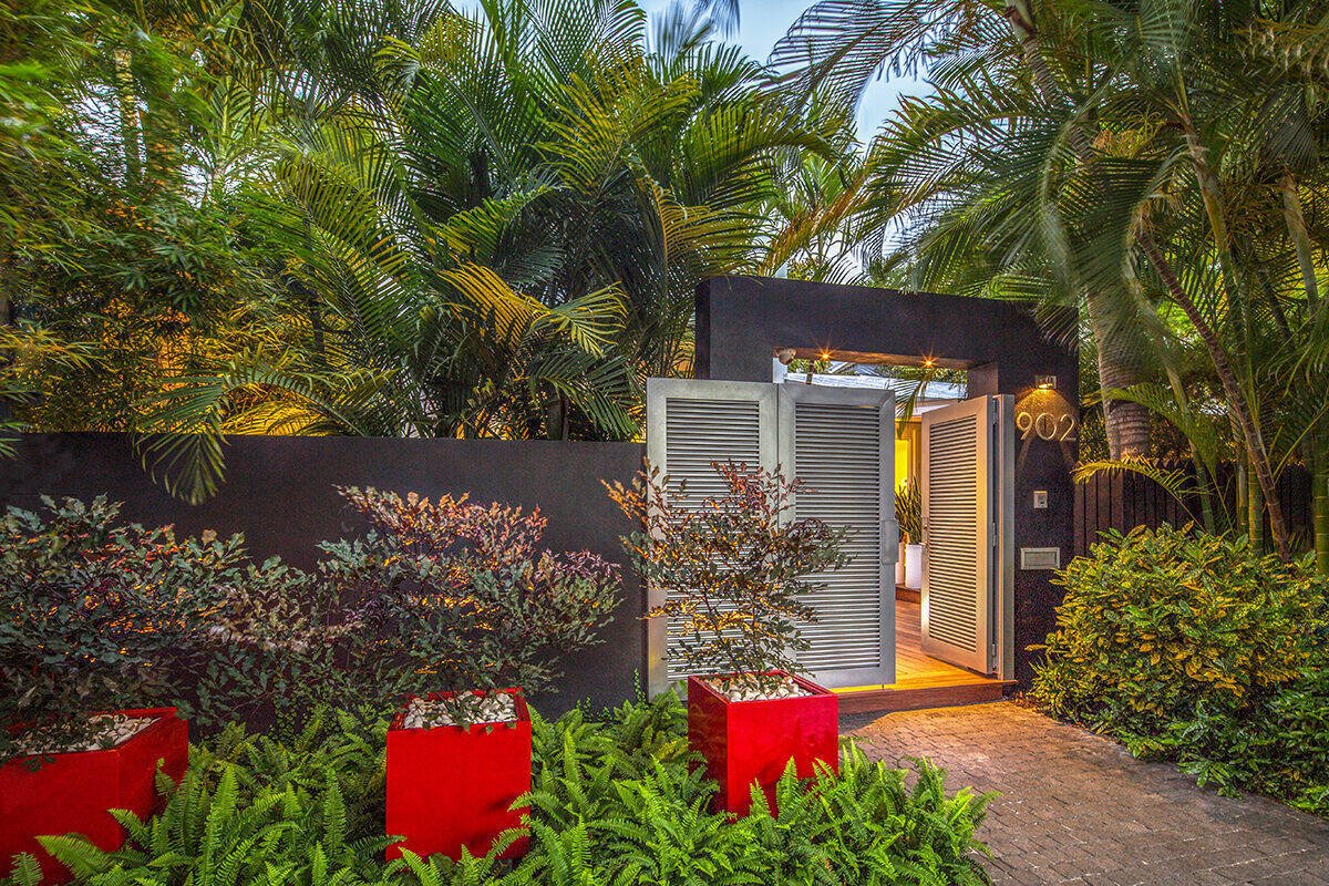 A dynamic entrance to the garden framed by mass plantings and bright sculptural containers sets the scene for the tropical garden behind the doors.  Von Phister by Craig Reynolds Landscape Architecture