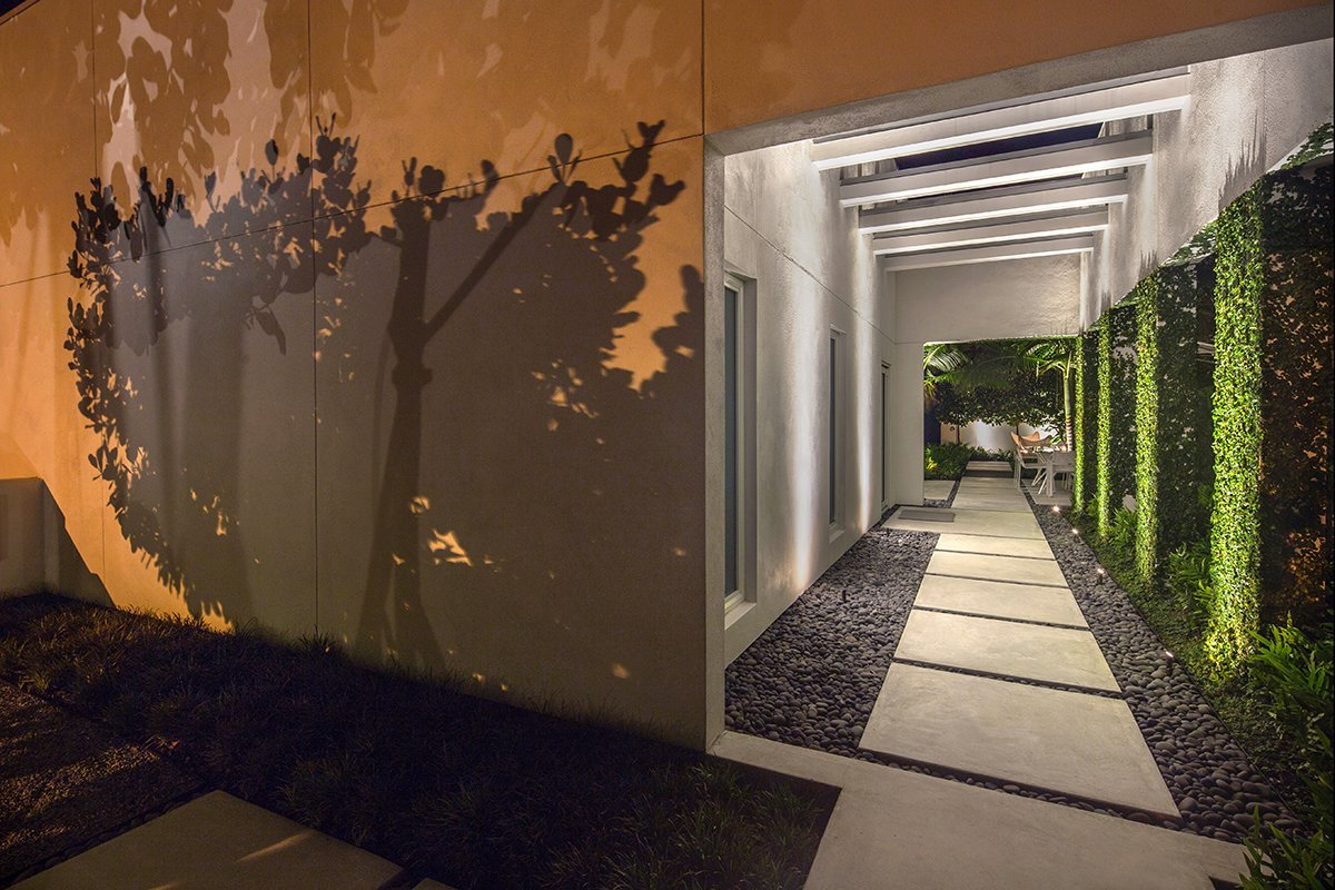 Outdoor, Front Yard, Walkways, Side Yard, Hardscapes, Trees, Concrete Patio, Porch, Deck, Small Patio, Porch, Deck, Pavers Patio, Porch, Deck, and Landscape Lighting Lighting is used to create drama, as well as, safety to this modernist retreat.  Tropical Minimal by Craig Reynolds Landscape Architecture