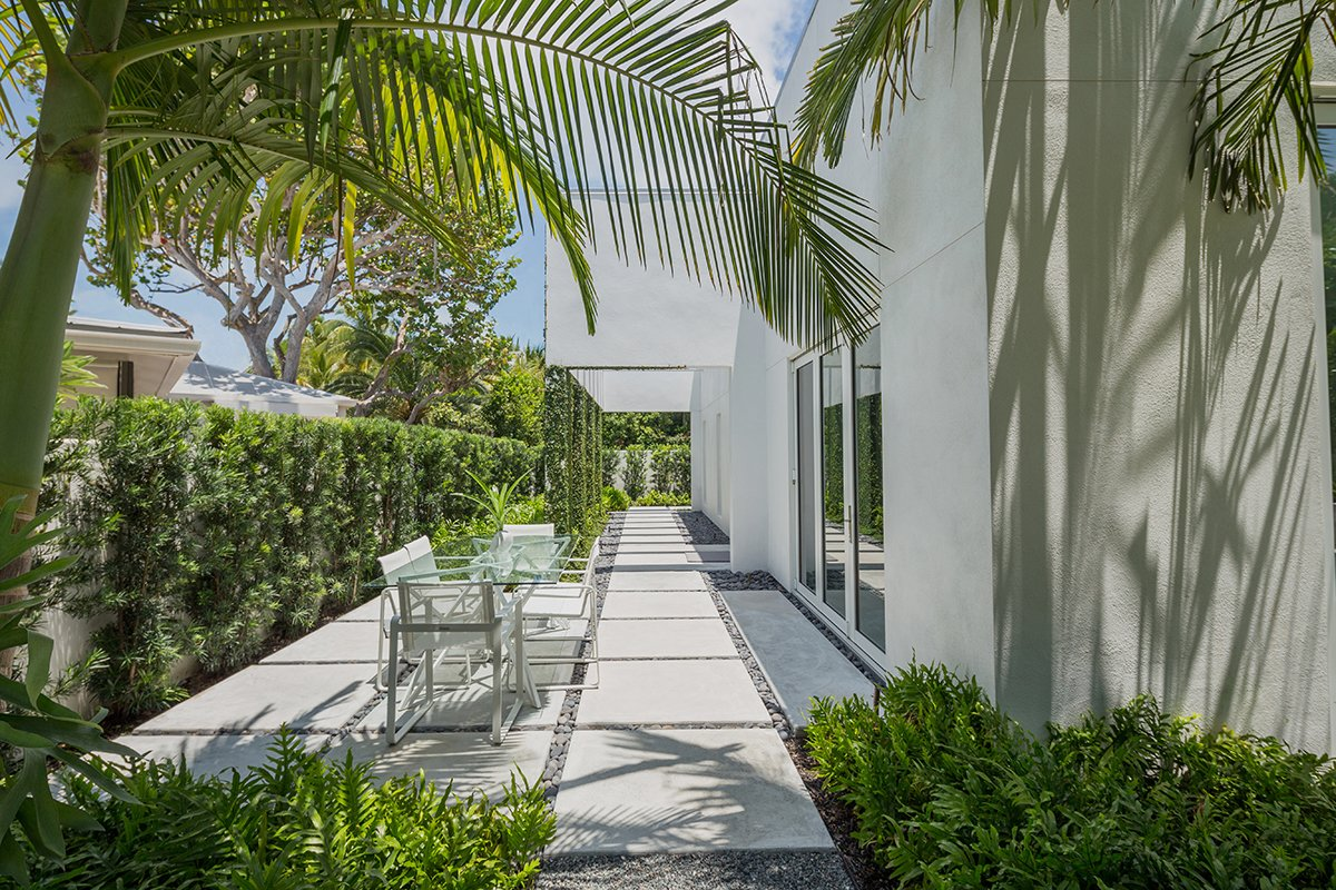 Outdoor, Shrubs, Trees, Side Yard, Walkways, Hardscapes, Landscape Lighting, and Concrete Patio, Porch, Deck Indoor/outdoor living is a must in Key West. The main design philosophy of the overall design was to create areas outside that acted as their own special spaces and were an extension of the inside.  Tropical Minimal by Craig Reynolds Landscape Architecture