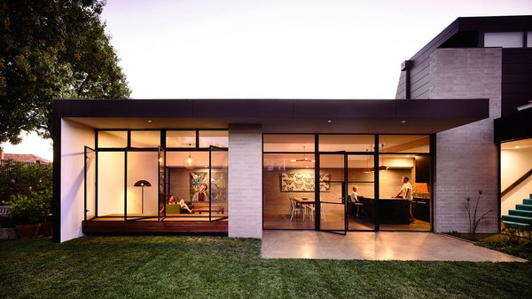 A steel-and-glass extension hosts the main living spaces and flows into the backyard.