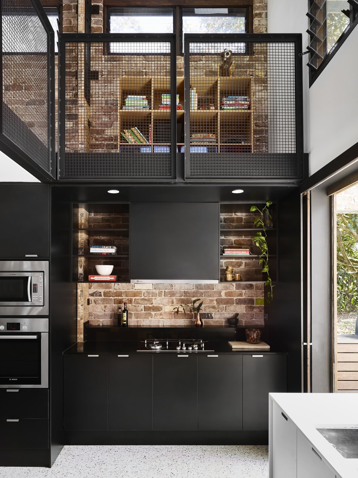 Kitchen, Engineered Quartz Counter, Terrazzo Floor, Granite Counter, Recessed Lighting, Brick Backsplashe, Microwave, Wall Oven, Cooktops, and Range Hood Here, a brick backsplash makes this black kitchen pop.   Photo 7 of 10 in Dwell's Top 10 Kitchens of 2017 from A Brisbane Architect Designs a Light-Filled Addition For Her Brother