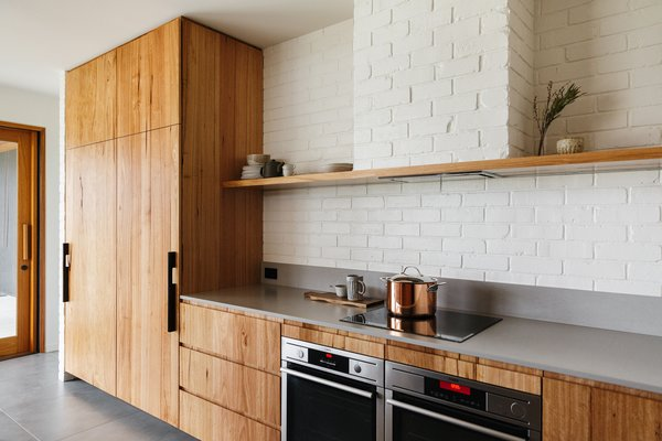 A brick backsplash, painted white, pairs perfectly with this Australian kitchen's understated material choices, which includes wood cabinets and a streamlined Caesarstone counter in Raw Concrete.