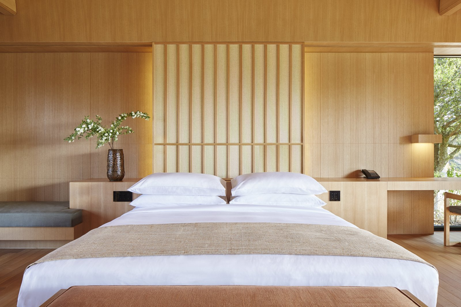 Bedroom, Bed, Night Stands, Bench, Chair, Wall Lighting, and Light Hardwood Floor Sliding glass doors and screens pull open to present framed views of nature, including the surrounding forests, private gardens, and the waters of Ago Bay. In the bathroom, deep stone tubs offer a private onsen experience, with the taps drawing water from nearby hot springs. When not soaking, step onto covered verandas to enjoy the natural surroundings at your leisure.  Photo 4 of 10 in A Sleek Resort in a Japanese National Park Reinterprets Tradition