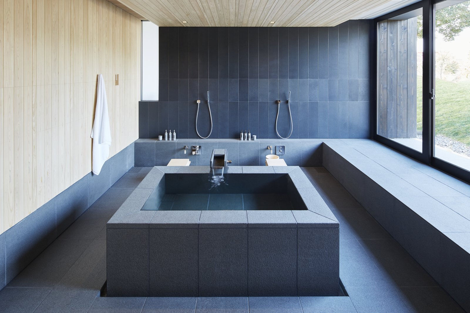 "Bath Room, Freestanding Tub, Recessed Lighting, Slate Floor, and Stone Tile Wall In a 2006 address, Kerry Hill said this of his firm's work, which could also apply to Amanemu: ""We reference past building traditions through suggestion and association rather than replication, and through the reinterpretation of indigenous building forms as opposed to mimicry. We prefer to build upon what is there and to contemporize our understanding of what it can be. I think of it as being current, but filtered through a sieve of traditional values. In this way it is familiar to people, but not quite the same. It is new, but connected to the past—hopefully in spirit, at least.""   Photo 7 of 10 in A Sleek Resort in a Japanese National Park Reinterprets Tradition"