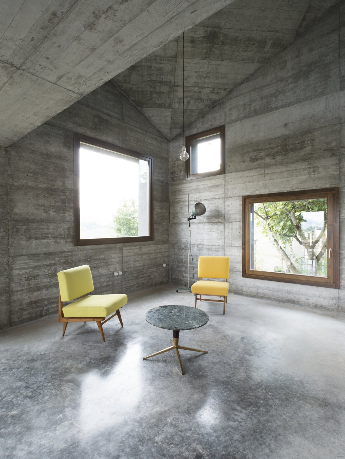 Chair, Concrete Floor, Pendant Lighting, Coffee Tables, End Tables, Floor Lighting, and Living Room An Italian architecture studio offers an updated take on the vacation cabin.  It's an ideal setting for a getaway: rolling hills dotted with villages and castles in Italy's Oltre Po Pavese region. A young Milanese couple wanted a small vacation home on their 3000-square-meter lot there—and 35a Studio delivered, by way of this 120-square-meter cabin decked out in textural concrete and strategically accented with wood.  Photo 21 of 25 in 25 Modern Homes That Kill it With Concrete
