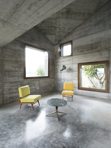An Italian architecture studio took advantage of an ideal setting for a getaway: rolling hills dotted with villages and castles in Italy's Oltre Po Pavese region. A young Milanese couple wanted a small vacation home on their 3000-square-meter lot there—and 35a Studio delivered, by way of this 120-square-meter cabin decked out in textural concrete and strategically accented with wood. While its exterior offers a smoother, stuccoed appearance, its interiors give way to a juxtaposition of two different concrete applications, opting for a rougher, board-formed treatment on the walls and a quartz paste polish on the floors. Wood accents, by way of the trimwork, doors, and cabinetry, provide rich, striking counterpoints.