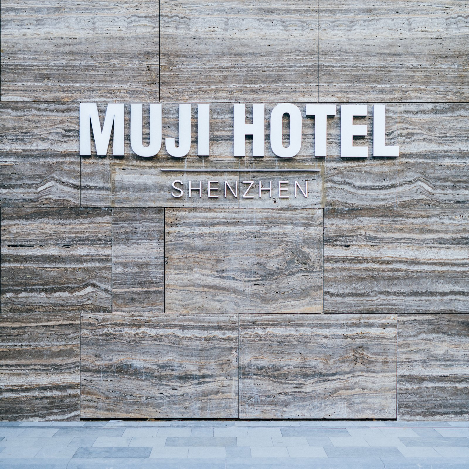 """Exterior and Stone Siding Material The hotel is sited near the downtown area in a multi-use complex. Seventy-nine rooms are combined with an on-site gym, library, diner—and a two-floor Muji store is the cherry on top for a complete immersion into the Muji experience. The brand sums up its new hospitality concept as both """"anti-gorgeous and anti-cheap"""": """"The goal is to offer great sleep at the right price, provide a space supporting both body and soul while away from home, and connect travelers to local communities.""""  Photo 1 of 10 in Be the First to Stay in the New Muji Hotel in Shenzhen"""